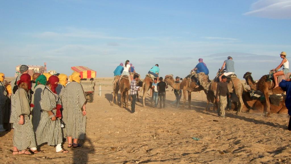 Zur Pegase-Touristenstation an den El Hofra-Dünen kommen die Busse aus den Pauschalhotels der Küstenorte. Man steigt aus dem Bus, bekommt ein Berber-Gewand, ein Dromedar und los geht´s in die Sahara.