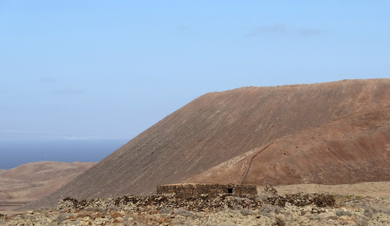 Am Fuße des Calderon Hondo stoßen wir auf restaurierte alte Hirtenbehausungen. Dahinter der Vulkan Bayuyo und das Meer bei Corralejo